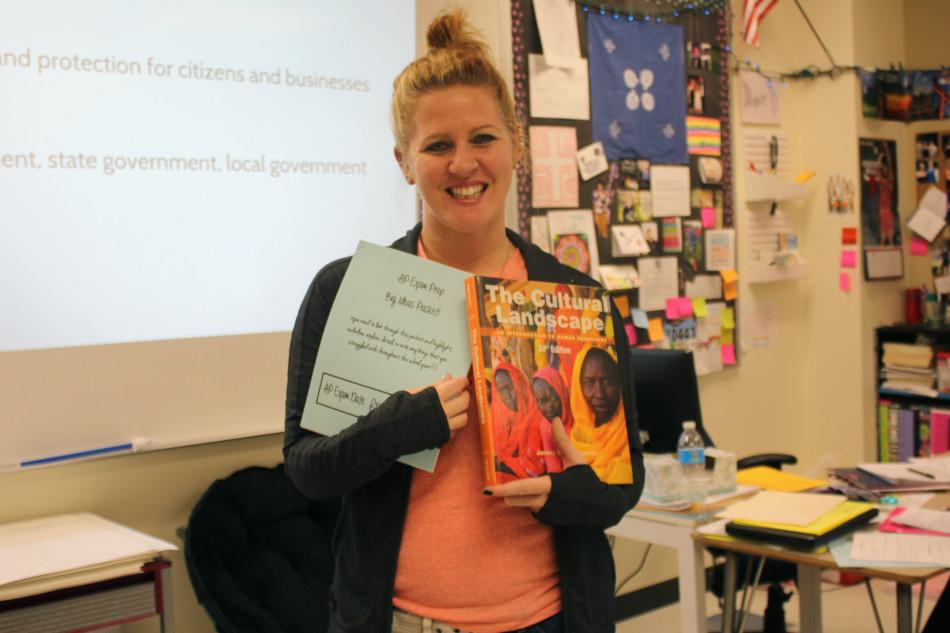 Mrs. Amanda Schuyler, Geography,  holds an AP Human Geography book and study guide. Mrs. Schuyler is one of the two AP Human Geography teachers.