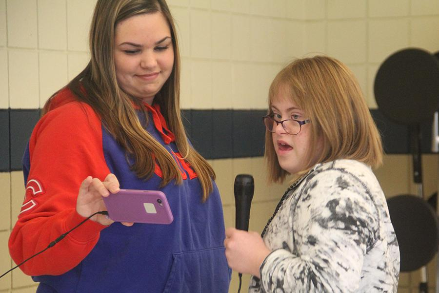 Hayley Rugis (12) holds a phone for Sarah Logan (12) to sing. Logan sang a song by Taylor Swift.