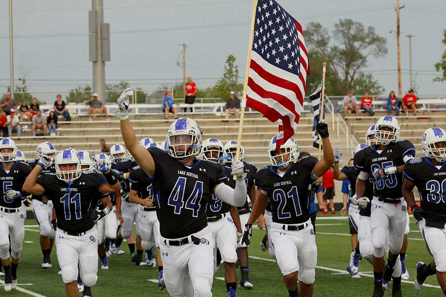 The varsity football team enters the field loud and proud with the American flag in hand. Their team had their kick-off after the parade.