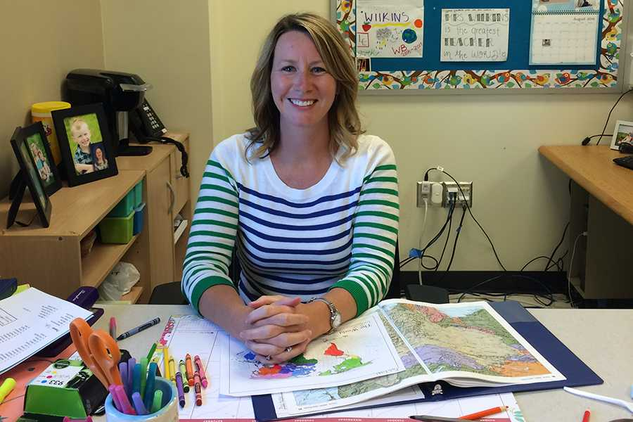 Mrs. Wilkins poses at her desk. She was in the process of grading maps for her AP Human Geography class.