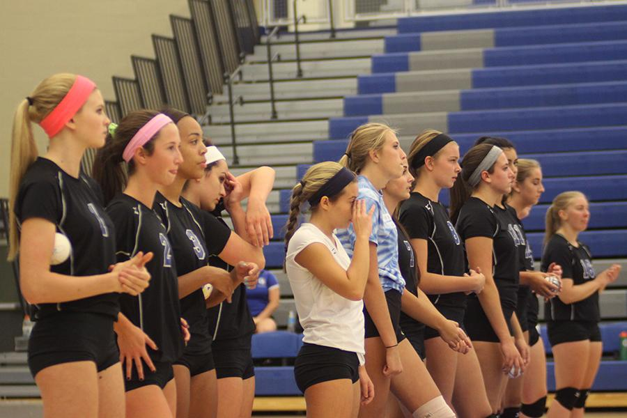 The varsity volleyball team stands waiting for their home opener to begin. The girls won all three sets.