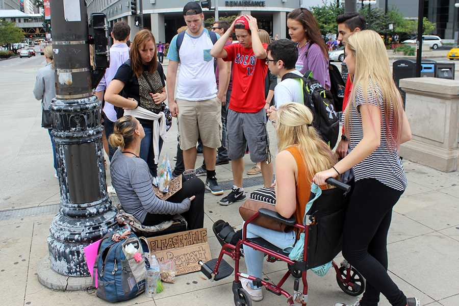 A group of students from Younglife speak with a homeless man. They handed out socks to the homeless on Saturday, Sept. 24th.
