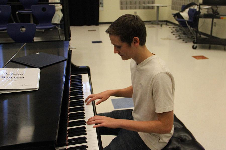 Mason Crawford (11) plays the piano before class begins. Mason has been waiting for school to start so he could show off his skills at Open Mic Night.