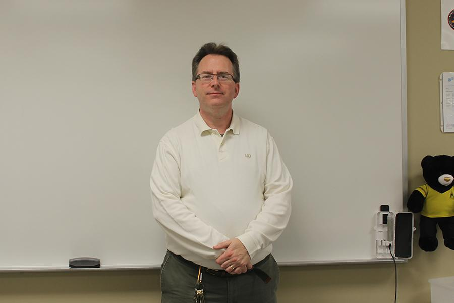 Mr.+Harnish+stands+in+his+high+school+classroom.+He+has+been+teaching+college+courses+at+Indiana+University.+