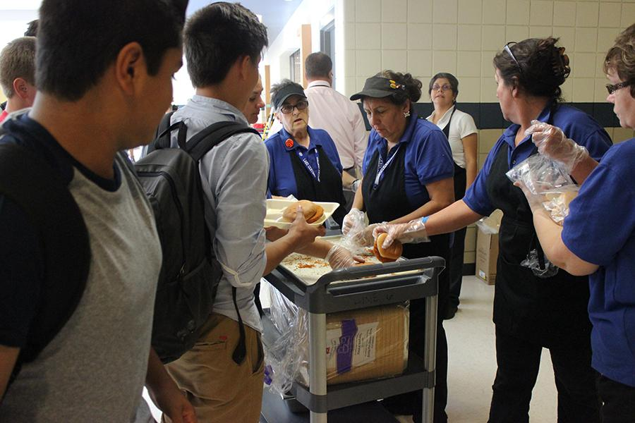 Members+of+the+cafeteria+staff+hand+out+chicken+sandwiches+to+students+during+D+lunch.+The+staff+was+unable+to+make+lunches+because+of+a+sewage+problem+on+Monday%2C+Sept.+26.