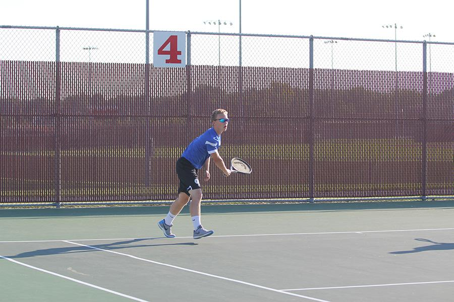 Noah Meyer (12) finishes his serve. Meyer played a double with Evan Leatherman (12).