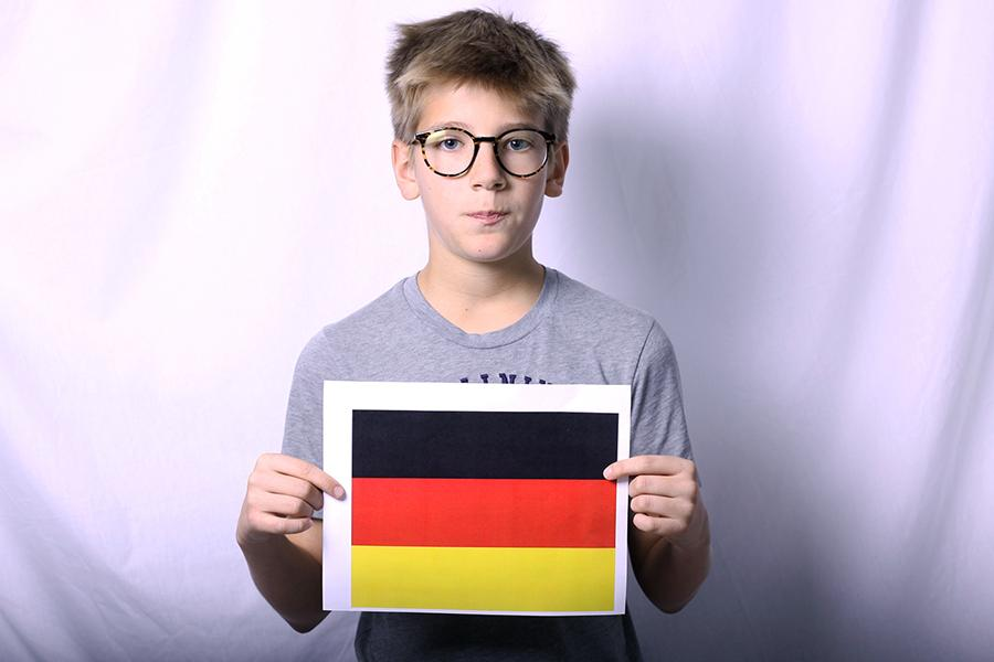 Paul+Jochmann+%289%29+poses+for+the+photo+as+he+holds+a+paper+with+the+German+flag+on+it.++Jochmann+was+not+been+very+excited+about+his+move+to+America.%0A