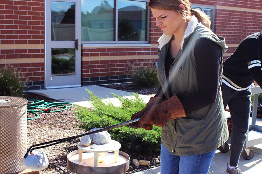 Abigail Sebahar (12) transports her piece into a trash can filled with fire. Sebahar fired three pieces.