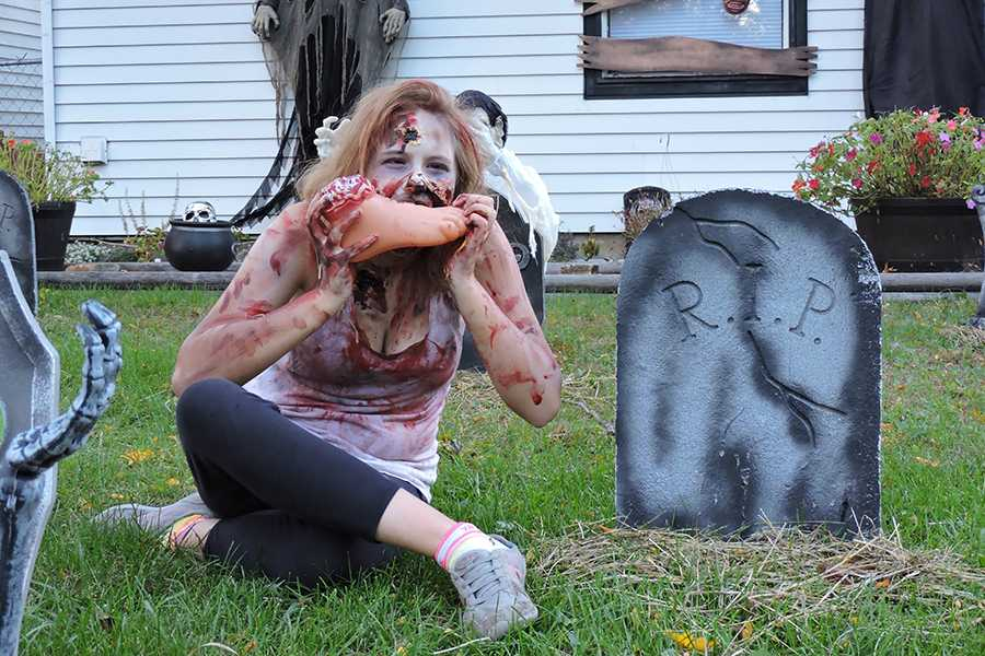 Paige Varady (9) dresses as a zombie and pretends to bite a fake foot. Varady made sure that just the right amount of fake blood was used on her makeup.