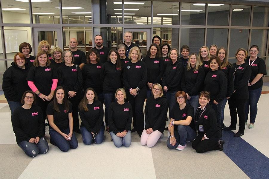 Staff members pose for a photo with the shirts purchased for the fundraiser. Mrs. Erin Novak, Dean of Students, designed the shirts. Photo submitted.