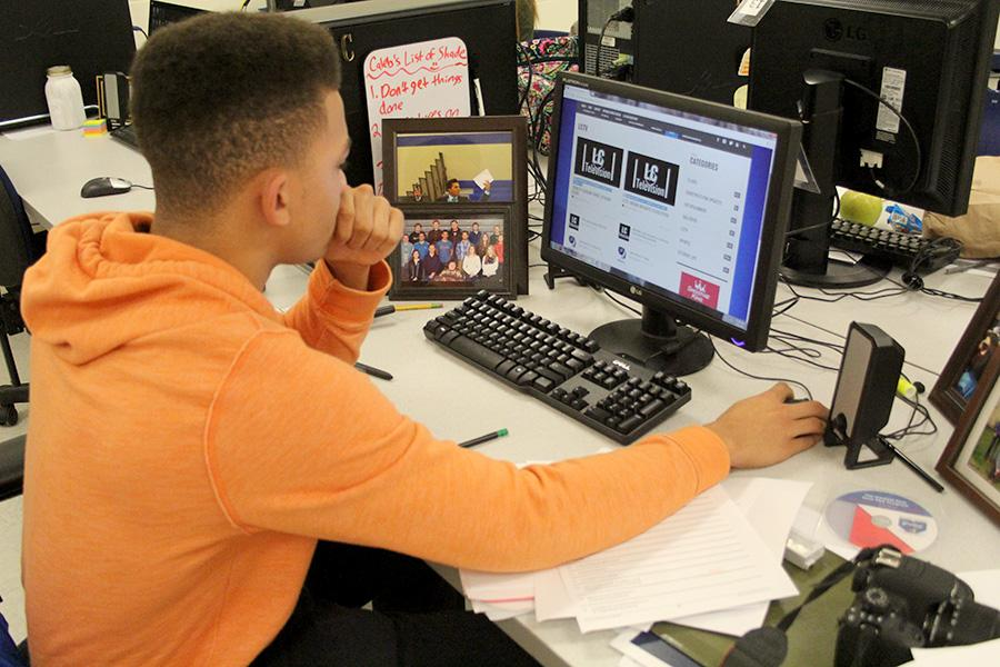 Caleb Beasley (12) looks at his computer during class. Beasley is one of the two Editor in Chief of Operations in the class.