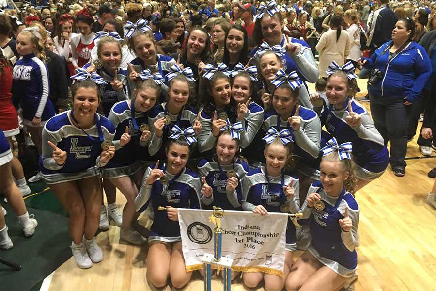 The+junior+varsity+cheerleading+team+poses+with+their+first+place+state+trophy+and+banner.+The+team+was+the+first+JV+team+from+Lake+Central+to+win+state.