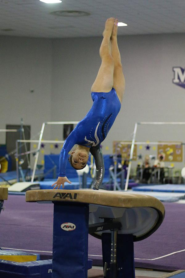 Maya+Tobin+%2812%29+pushes+off+of+the+vault+during+the+meet.+Tobin+placed+sixth+in+vault+with+a+score+of+8.25.%0A