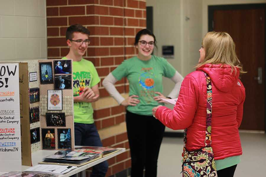 Adam Gustas (12) and Hannah Souronis (12) talk with a parent about the opportunities that the Lake Central Theatre Company offers. Booths for multiple clubs and organizations were set up with students for parents to get information from.
