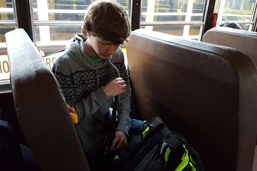 Brendon Tomky (10) buckles his seat belt for the ride home from school. As of Jan. 9, Lake Central has equipped their buses with seat belts as an extra safety measure.