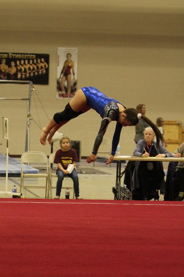 Abby Ispas (12) does a front tuck during her floor routine. The team competed Tuesday, Feb. 7.