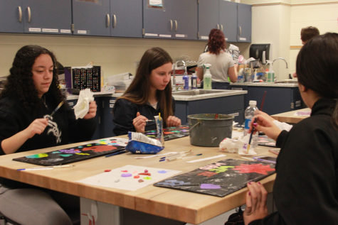 Students continue to work on their individual projects. After the painting had dried, they were able to scrape off their paintings and use them as window decals.