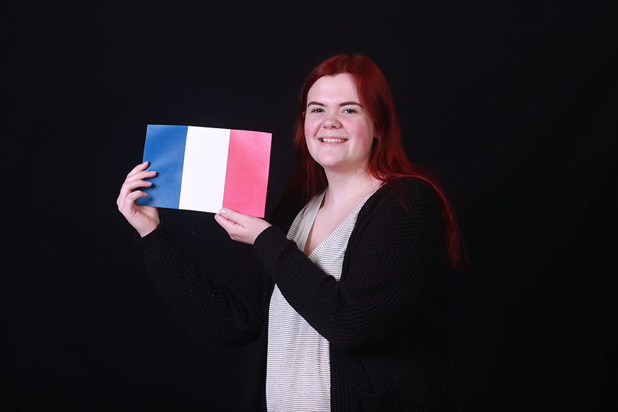 Lauren Kamykowski (11) holds up the French Flag. Kamykowski applied for the IUHPFL program to stay in France for seven weeks over the summer.