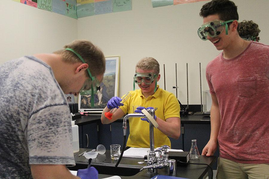 Nathan+Jackson+%2812%29+pours+a+measured+solution+from+a+graduated+cylinder+into+an+empty+beaker.+One+of+his+lab+partners%2C+Kyle+Holman+%2812%29%2C+took+notes+in+his+notebook.