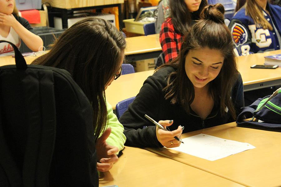 Madison Spoerner (10) and Brianna McCormack (10)  sign in for Interact. The club has helped start many fundraisers in the past, including Buds for Bossi.