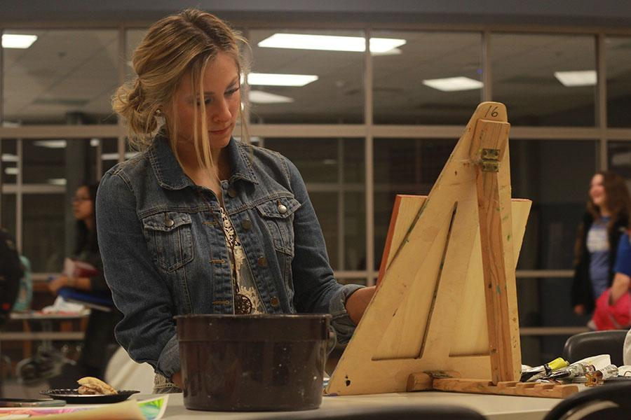 Kayla Martin (11) paints a sunflower onto a canvas. Throughout the night, fine arts students showcased their talents and abilities for all attendants to see.