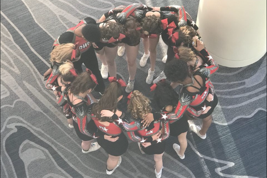 Midwest Elite's cheerleaders join together for a group prayer before they compete. They won first place at their most recent competition.