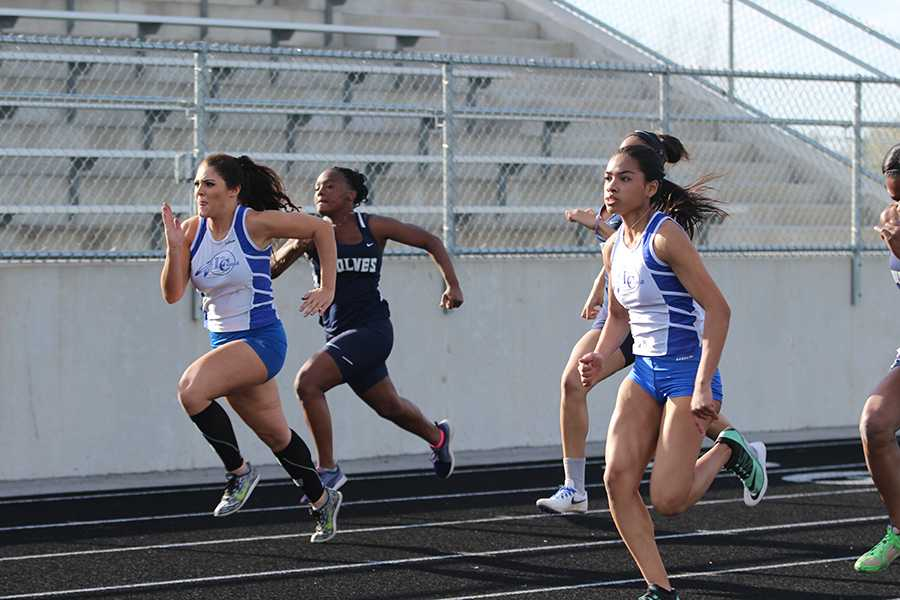 Kelani Benson (11) and Taylor Dykstra (9) run the 100 meter sprint. The girls had several freshmen running in the varsity level this year.
