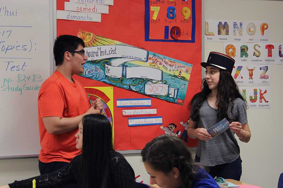 Theodore Mantis (10) tells Autumn Flenar (10) the significance behind the French police hat she is wearing. Flenar won the prize of wearing the hat for the duration of the meeting after being the first to complete a crossword puzzle.