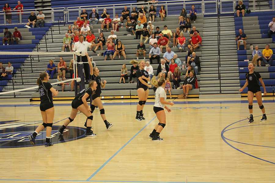 The girls jump in excitement after scoring a point during their match against Crown point. Amanda Robards (11) had just made a kill.