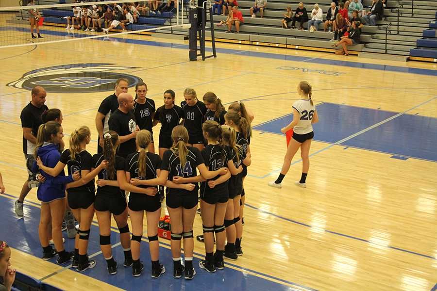 Varsity+Volleyball+comes+together+for+a+team+huddle+during+a+timeout.+Coach+Matt+Clark+gave+them+a+pep+talk+during+the+timeout.