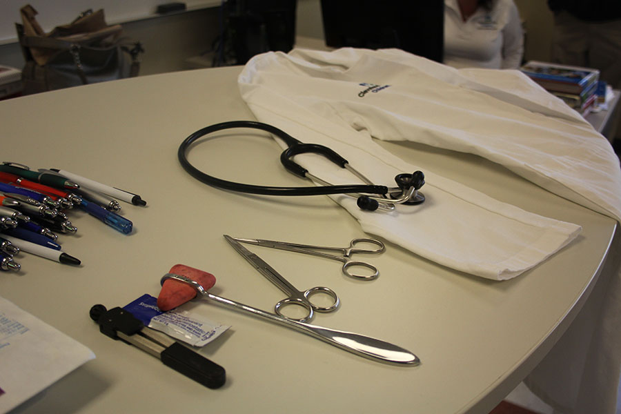 A white coat, stethoscope and other medical tools lay across the table. A nurse practitioner came in from Cleveland Clinic to talk to Future Medical Professionals about her career.