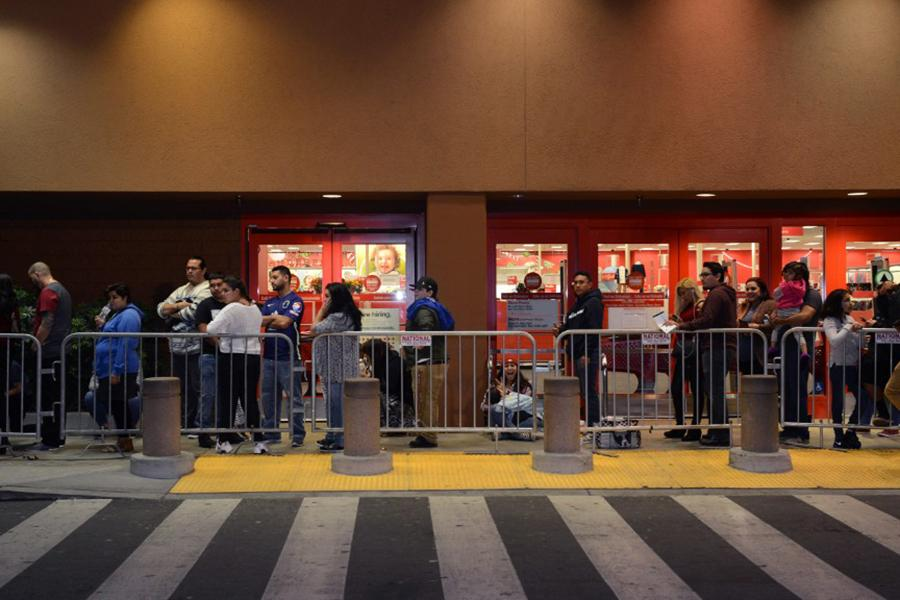 Shoppers wait in line for the store to open. The sales brought many people in hopes to find what they need.