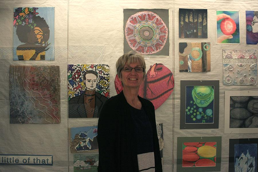 Mrs. Maureen Yaeger, Art, stands in front of the art case in the hallway. This case was filled with art student's previous projects.