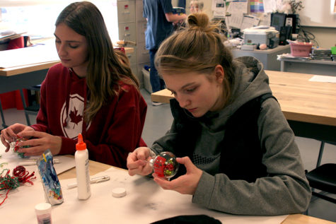 ey Imming (10) and Paige Covelli (9) finish decorating their ornaments. The activity of the meeting was to make and decorate Christmas ornaments.