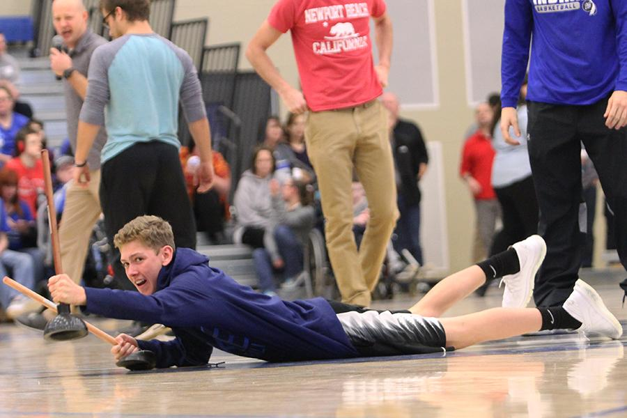 Brock Bevil (10) drags himself across the gym floor with toilet plungers. The sophomore class team won the plunger race.