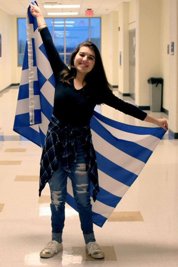 Andrea+DeCastro+%2811%29+proudly+poses+with+her+Greek+Flag.+The+flag+was+a+gift+she+received+from+her+mother+to+hang+in+her+room.