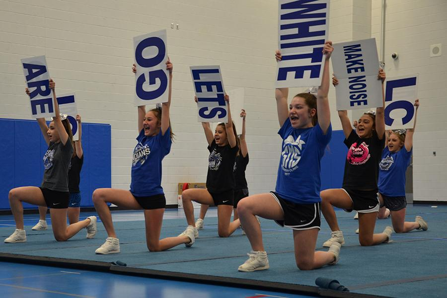 Brooke Bubash (9) [middle] practices their cheer using signs. Bubash was on the freshmen team last year.