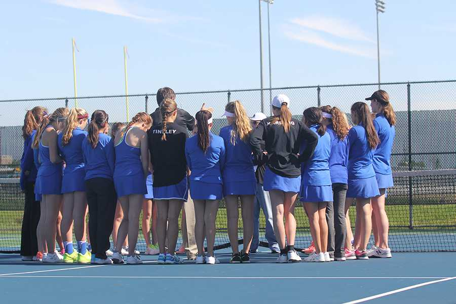 The girls tennis team huddles before a match. The team won their first Sectional championship in 14 years last season. Photo By: Camille Bereolos