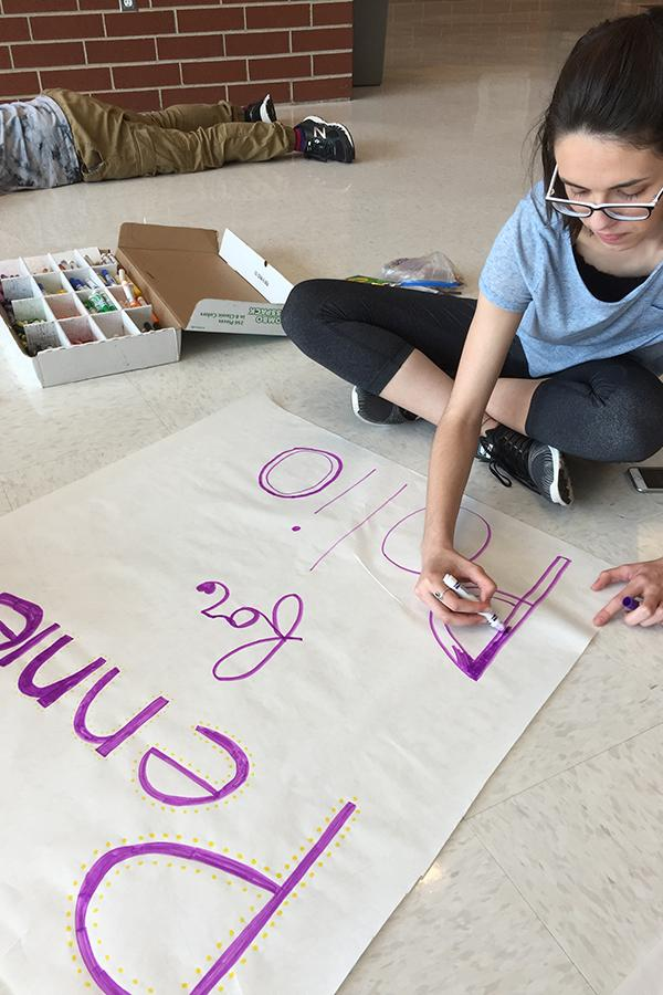 Morgan DeChene (10) coloring a poster for Pennies for Polio. There will be posters up around the school advertising students and staff to donate money to help people with polio.