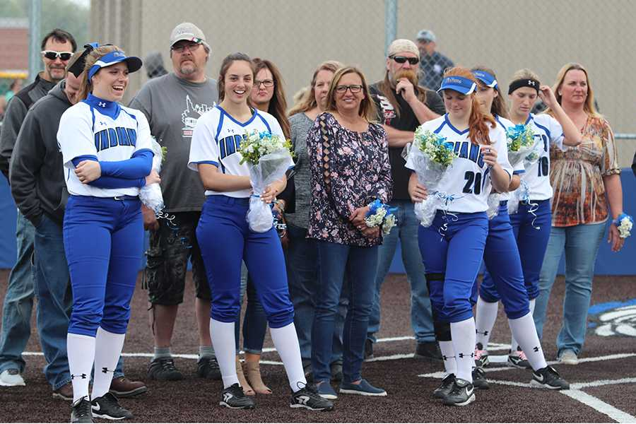The senior girls stand on the field with their families. The girls were given gift baskets after the game was over.