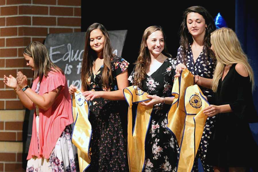 Madeline Andrews (12), Lauren Davidson (12), Courtney Carlson (12) and Megan Hraban (12) hold their graduation hoods. These girls all achieved Summa Cum Laude.