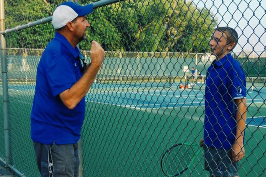 Lake+Central%E2%80%99s+Tennis+coach%2C+Ralph+Holden%2C+pulls+player+David+Spriggs+%289%29+aside+to+strategize+during+his+singles+match+against+Highland.+David+played+an+exciting+match%2C+defeating+his+opponent.+