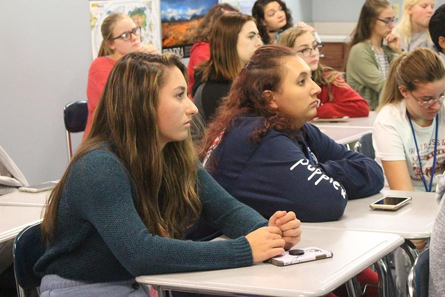 Cevanah Brazzale (12) and Mikayla Zivak (12) sit and listen to the Environment Club presentation. The club was held after school on Thursday, Sept. 13.