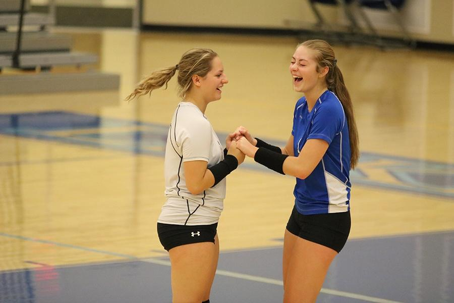 Sam Hurubean (11) and Mackenzie Kusbel (11) laugh during some down time. They played libero and outside hitter, respectively.