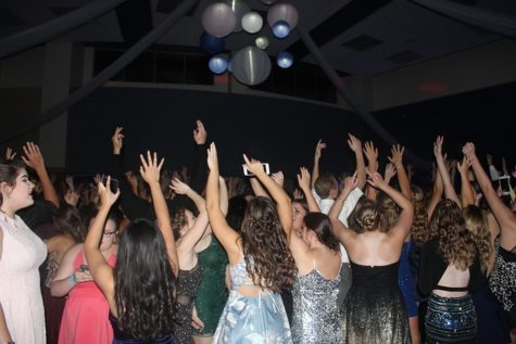 Students throw their hands up in the air. The  DJ played some hit songs from the 2000's. Photo by: Sarah Huszar