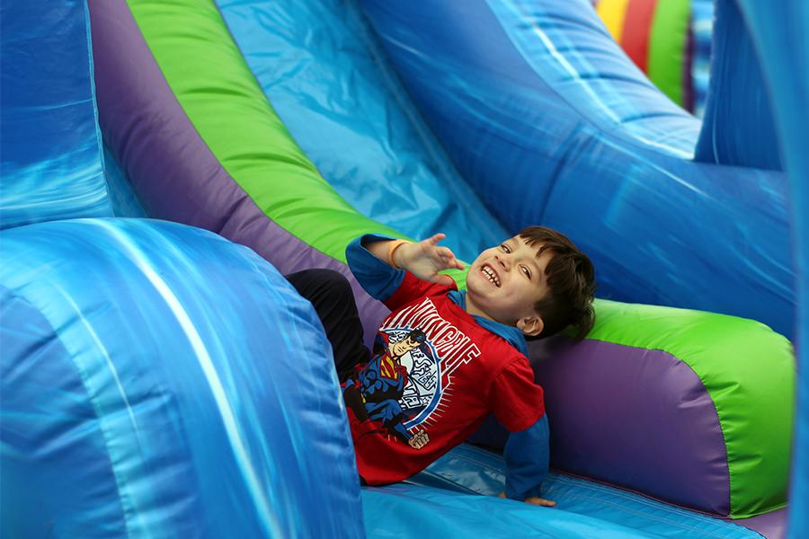 John Stock (Pre-K) smiles after descending down the slide. Stock enjoyed his afternoon by playing in the bouncy houses at the fest.