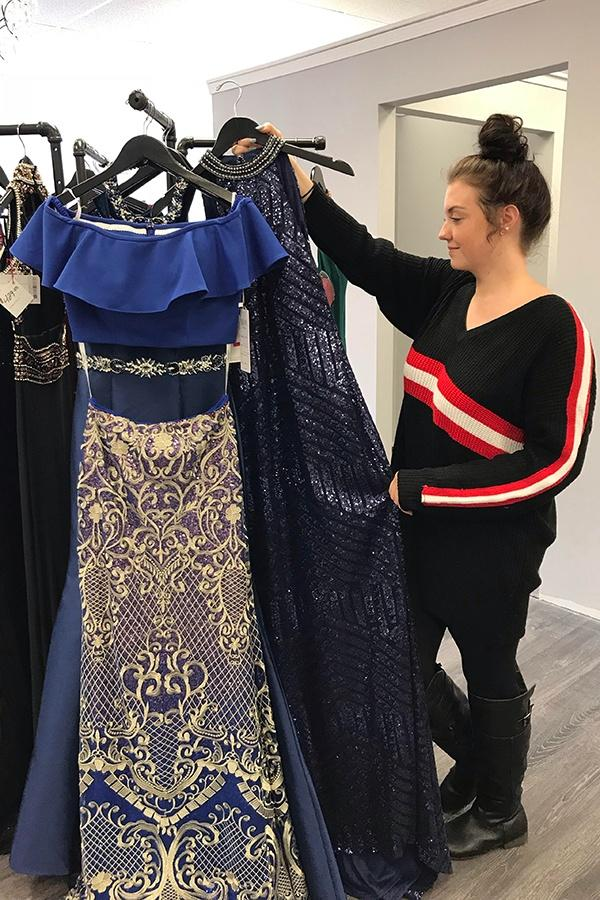 Grace Collinge (12) hangs up a dress during work. She got a job at Diva Dresses after she purchased her prom dress from the store.