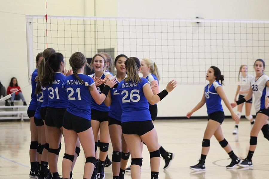 As the game begins, the girls high-five each other to get their energy up.  The girls won in two sets to Michigan City.