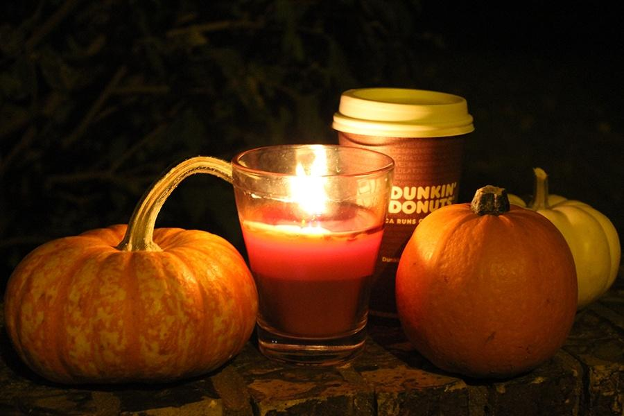 A pumpkin, coffee and candle are shown. October is known as Spooky Season.