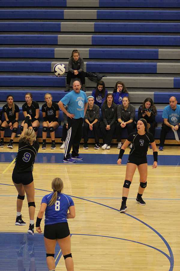 Emma Best (10) passes the ball over the net. Her teammates and coach watched anxiously waiting for her to make it over.
